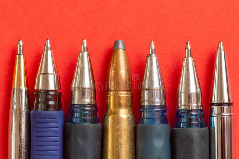 Bullet and pens on red background. Freedom of the press is at risk concept. World press freedom day concept.  royalty free stock images