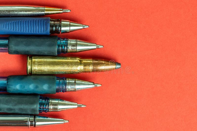 Bullet and pens on red background. Freedom of the press is at risk concept. World press freedom day concept.  stock image