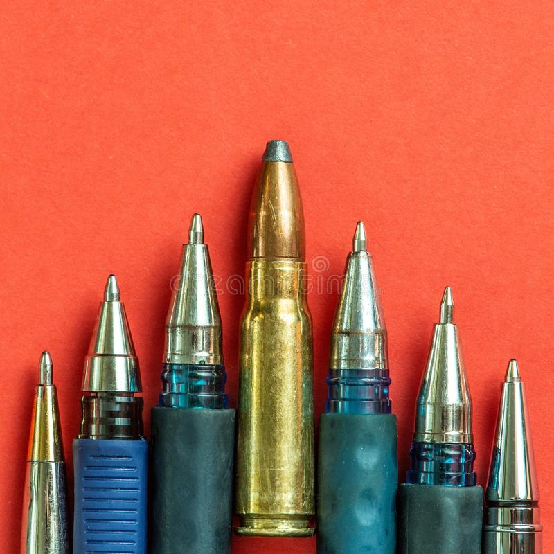 Bullet and pens on red background. Freedom of the press is at risk concept. World press freedom day concept.  stock photography