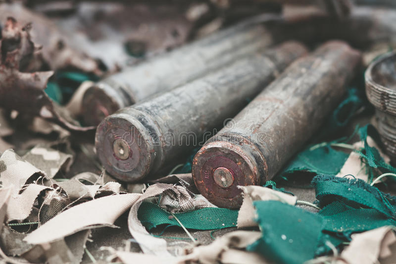 Bullet shells from heavy machine gun on the table with camouflage netting stock photography