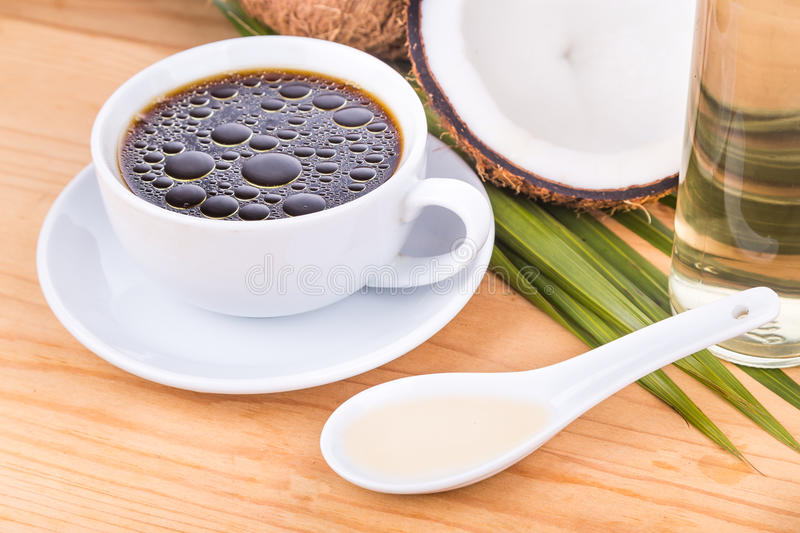 Bulletproof coffee with virgin coconut oil on wooden table. Closeup on bulletproof coffee with cold pressed extra virgin coconut oil on wooden table, part of stock photo