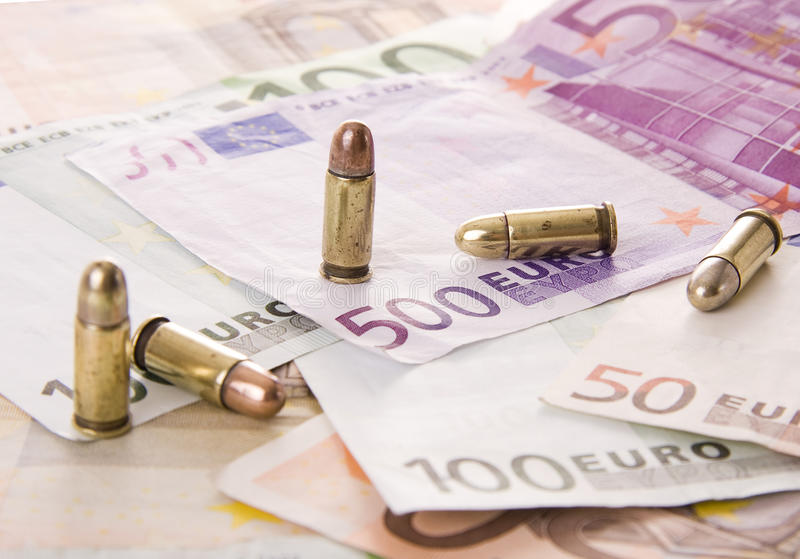 Bullets. Five bullets and euro banknotes - Selective focus on the 500 euros royalty free stock images