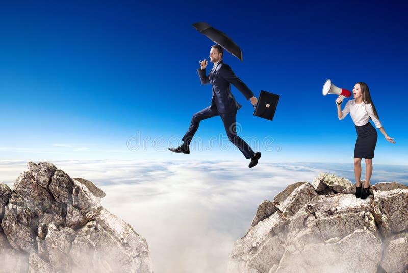 Το άλμα επιχειρηματιών πέρα από έναν απότομο βράχο και έναν συνάδελφο είναι ενθαρρυντικό με το bullhorn στοκ εικόνα