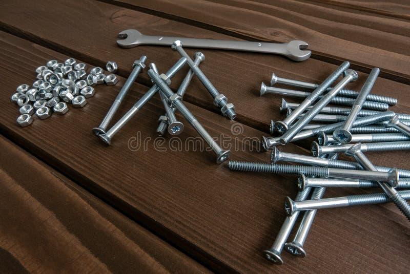 Bulloni lunghi e dadi del cromo che si trovano sulle plance di legno accanto alla chiave d'acciaio fotografie stock libere da diritti