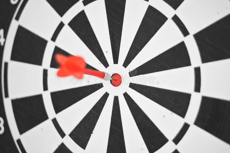 Bulls eye. A red dart stick in the very center of a target or the bulls eye royalty free stock photo