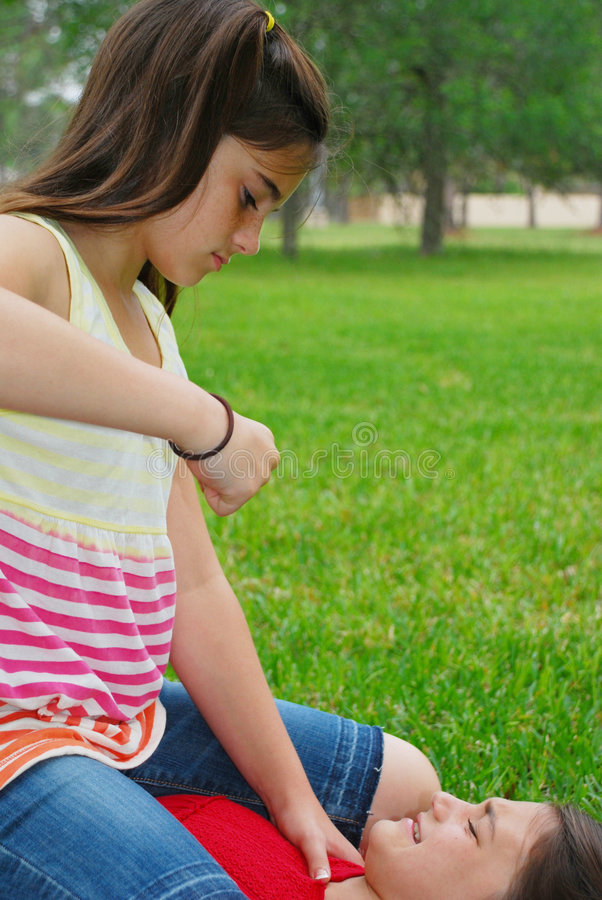 Bully. Older schoolgirl bullying a younger girl in the park stock photography