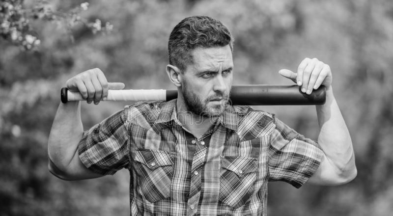 Bully guy in nature with cudgel. Wild energy. Power and strength. Feel my strength. Man unshaven strict face hold black royalty free stock photography