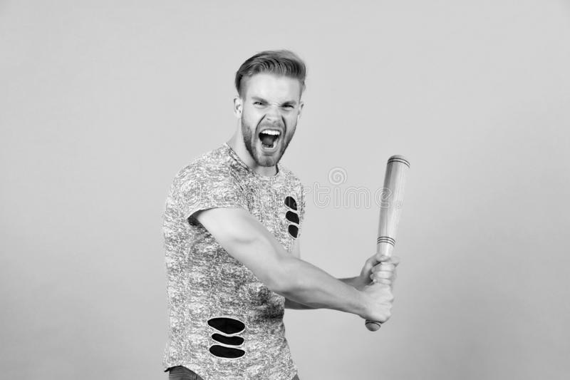 Bully man shouting aggressive face, grey background. Man with wooden bat ready to attack. Aggressive behaviour concept royalty free stock image