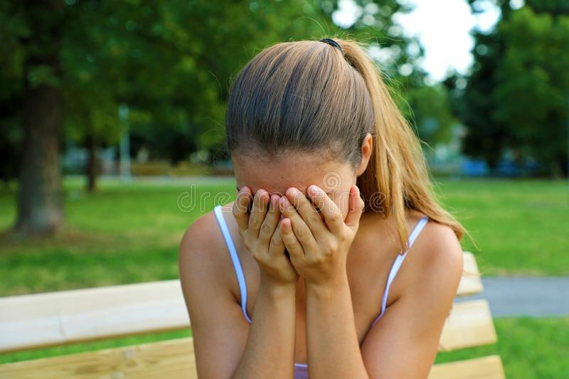 Bullying, discrimination or stress concept. Sad teenager crying alone in the park. Upset young female student having anxiety stock photos