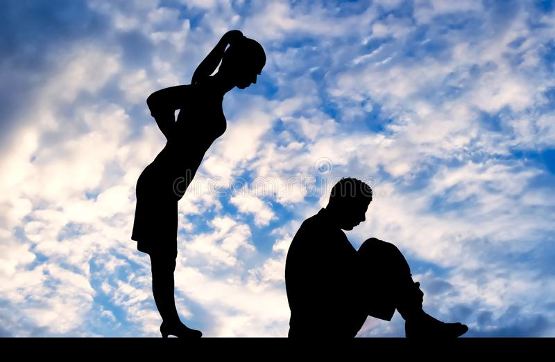 Bullying. Silhouette of scared man and angry boss woman. Workplace bullying concept. Silhouette of a frightened male worker sitting on the floor and a female royalty free stock image