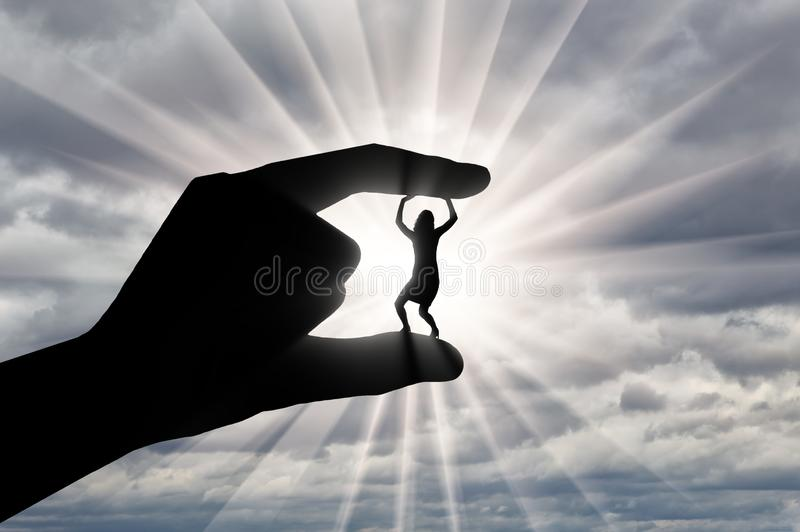 Bullying work. Silhouette of a hand holds between the fingers a woman. Who squirts against a cloudy sky. Workplace bullying concept stock images