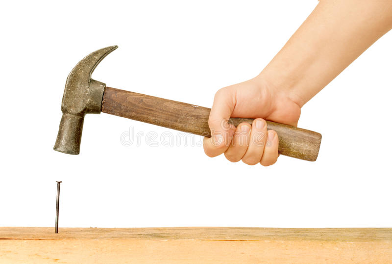 Bulta och spika genom att använda hammaren arkivbild