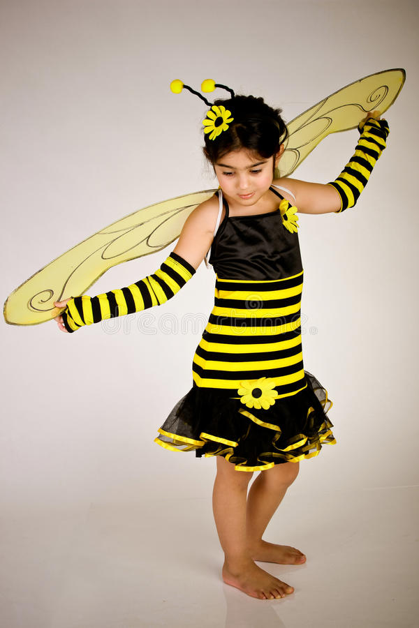 Bumble bee. Cute Little girl wearing a bee costume on white background royalty free stock image