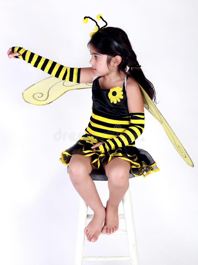 Bumble bee costume. Cute Little girl wearing a bee costume on white background royalty free stock images