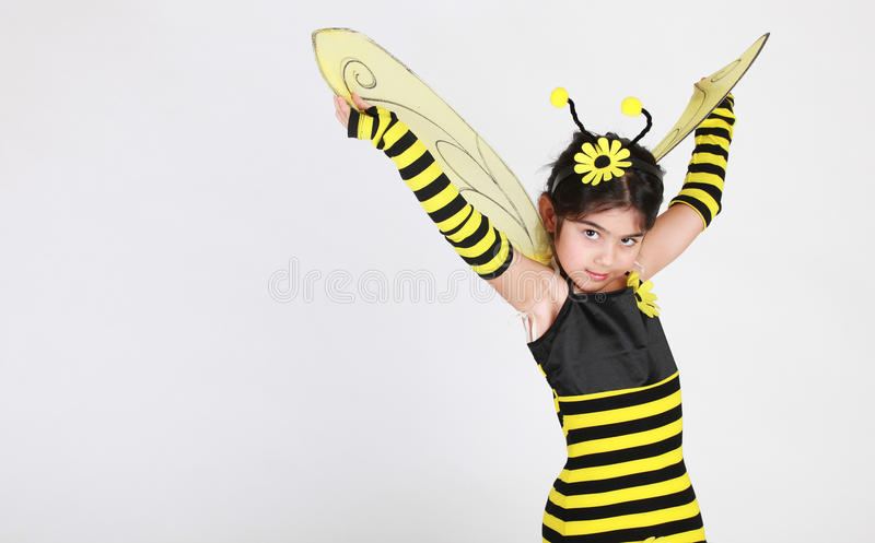Bumble bee costume. Cute Little girl wearing a bee costume on white background royalty free stock image