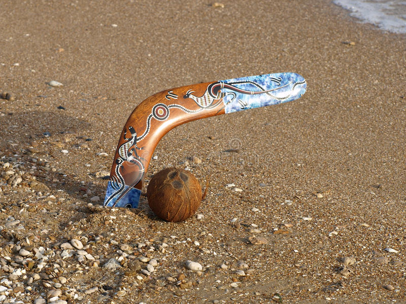 Bumerangue e coco em uma praia. foto de stock