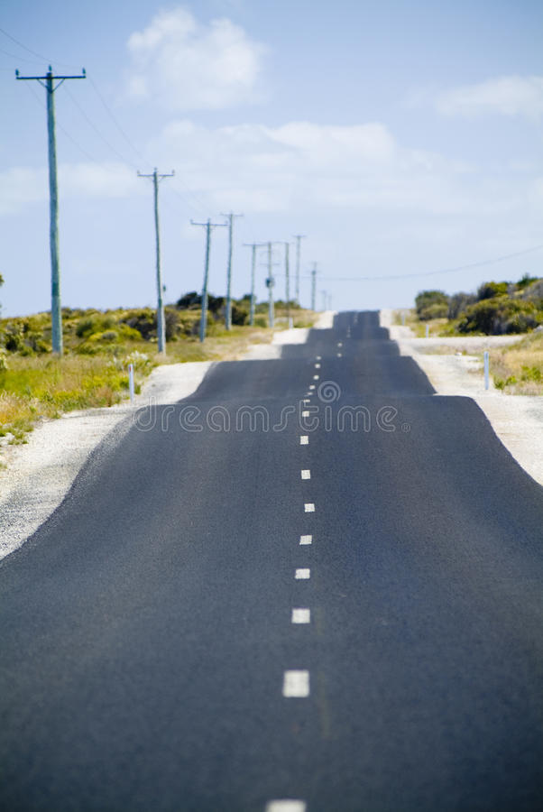 Bumpy Road. Very bumpy, rough road with power lines and blue sky royalty free stock photo