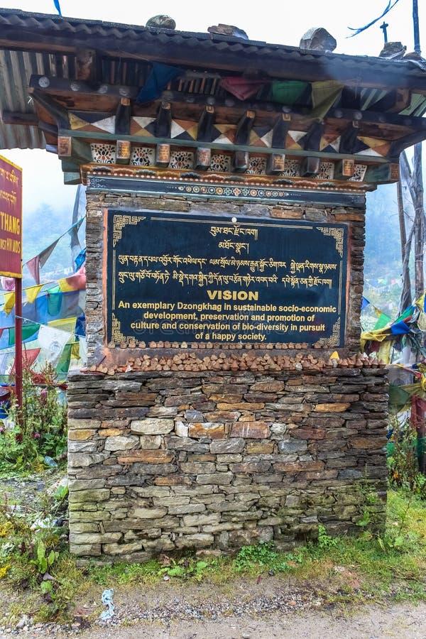 Bumthang, Bhután - 13 de septiembre de 2016: Estructura butanesa del estilo con el letrero que explica la visión de Dzongkhag en  foto de archivo libre de regalías