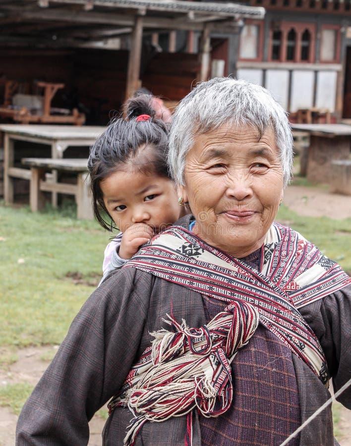 Bumthang, Butão - 14 de setembro de 2016: Mulher butanesa idosa que leva uma criança nela para trás em uma vila no vale de Bumtha fotos de stock