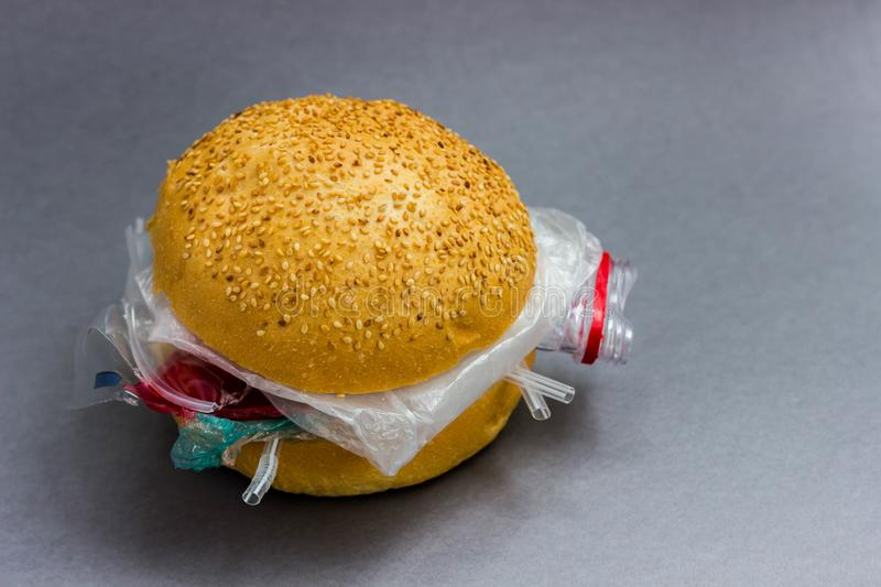 Bun with polyethylene and plastic instead of vegetables and meat. The problem of pollution of the planet with plastic. Ecological royalty free stock images