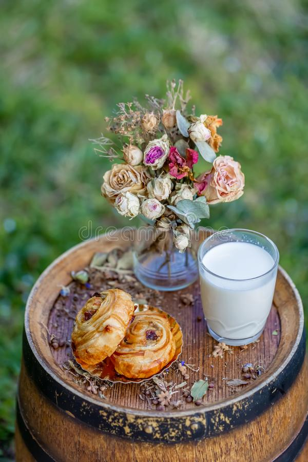 Bun with raisins and a glass of milk on old wine barrel. Dessert. Bouquet of withered flowers. royalty free stock photography
