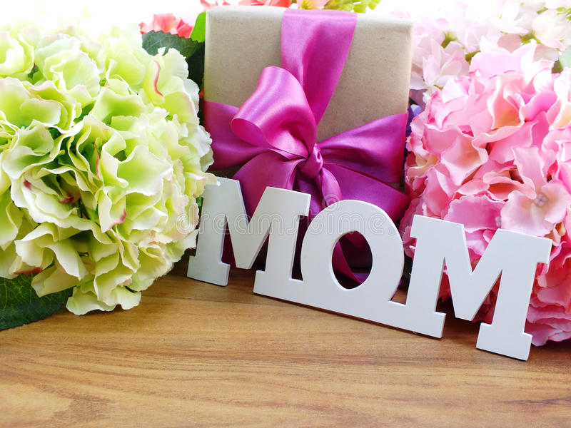 Bunch of artificial flowers with a gift box and word mama on wooden background stock photos
