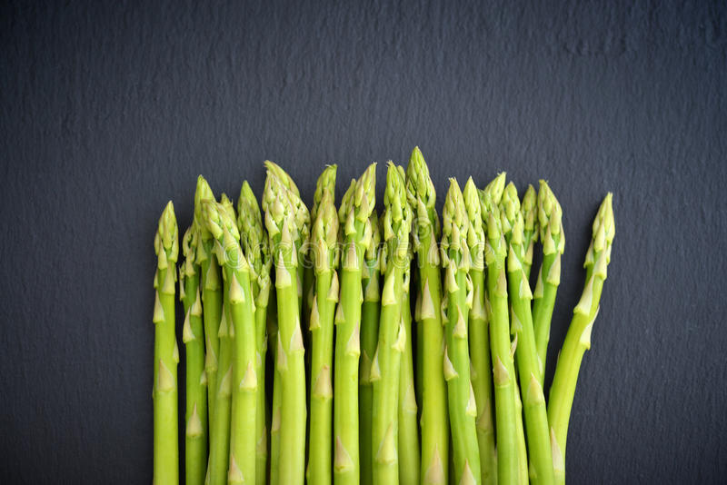 Bunch of asparagus. On black slate background, top view royalty free stock photos