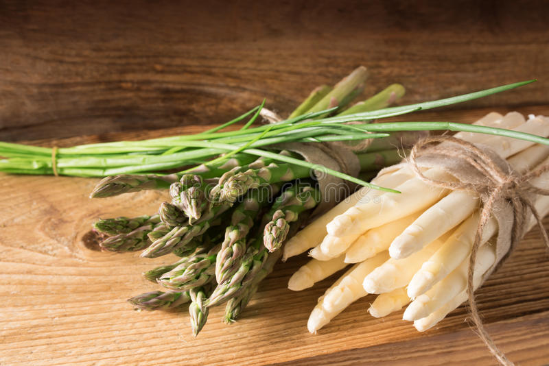 Bunch of asparagus with chives on wood stock images