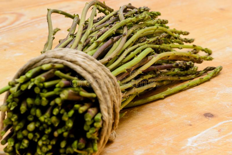 A bunch of asparagus tied with a cord on a wooden chopping board. stock photos