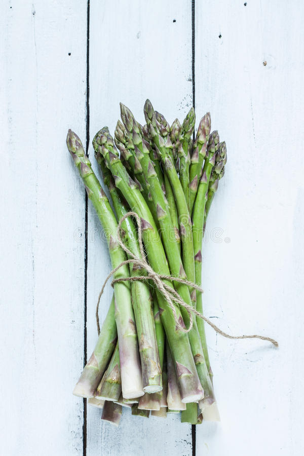 Bunch of asparagus on white planked wood table from above royalty free stock image