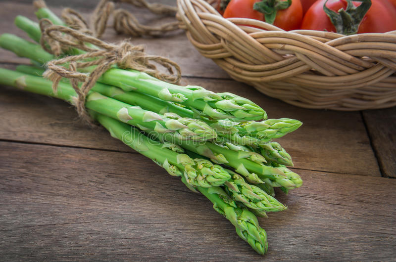 Bunch of asparagus on wooden table and tomato in basket royalty free stock photo