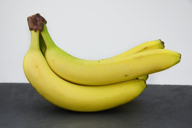 Bunch of banana`s on black slate. Bunch of yellow banana`s on dark black slate table. Healthy fruit. Vitamines a b c d royalty free stock image