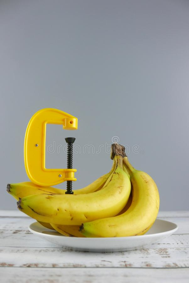 Bunch of bananas and clamp on wooden background. Copy space for text or logo.Vertical shot. Concept, cluster, fruit, green, yellow, delicious, fresh, object stock photo