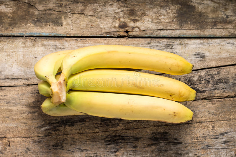 Bunch of Bananas on Grunge Wood Background. Top View royalty free stock photography