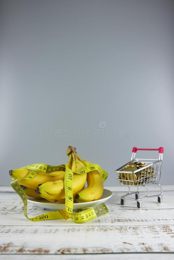 Bunch of bananas,measuring tape and shopping cart full of coins on wooden background. Copy space for text or logo. Sale, wellness, trolley, store, loss stock photos