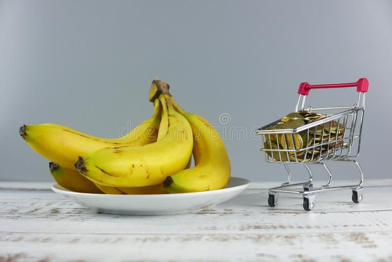 Bunch of bananas with shopping cart full of coins on wooden background. Sale, wellness, trolley, store, center, supermarket, wallet, retail, commercial, cash stock image
