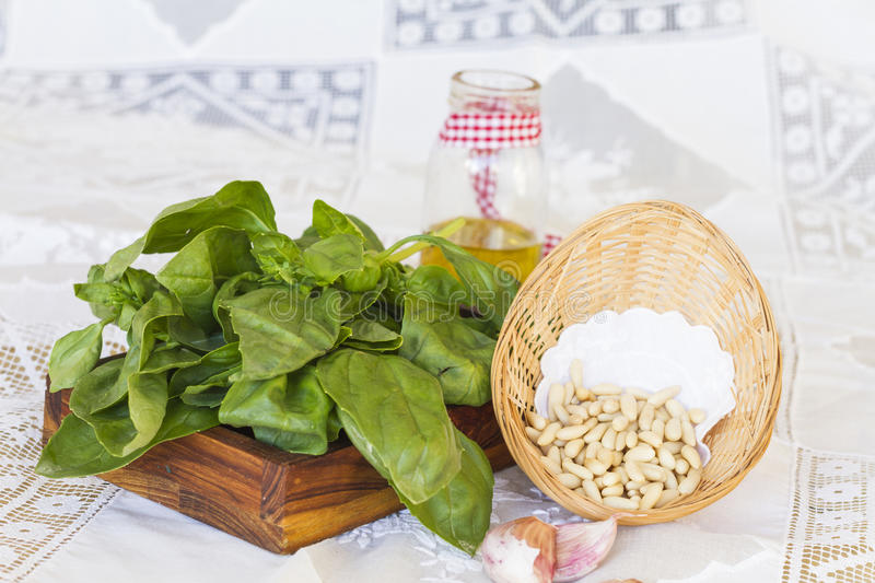 Bunch of basil with pine nuts on wooden tray stock images
