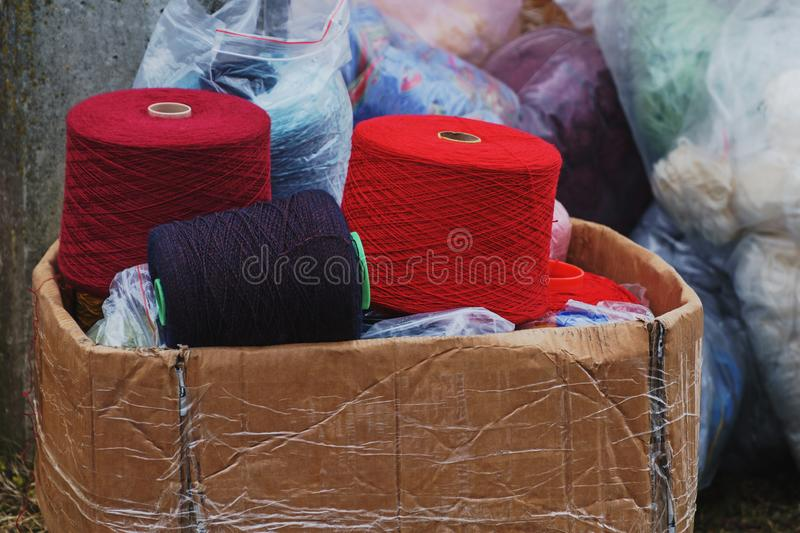 A bunch of big colorful thread spools in old carton box royalty free stock image