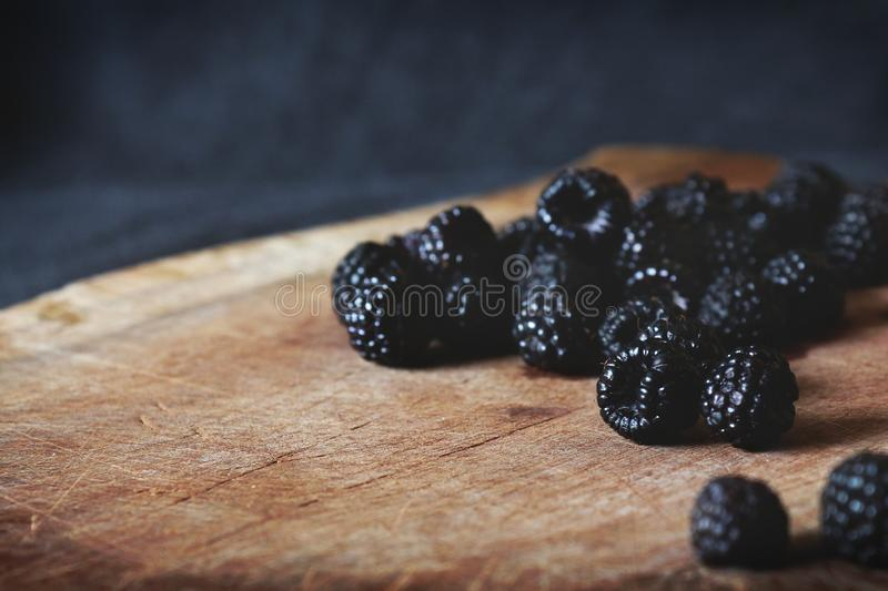 A bunch of blackberries on the cutting board with black background behind royalty free stock photos