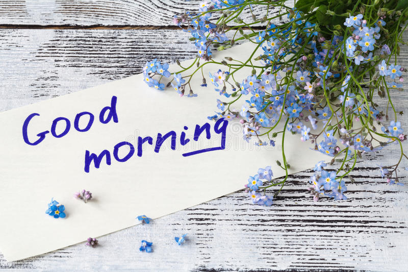 Bunch of blue flowers forget-me-nots and good morning note stock photography
