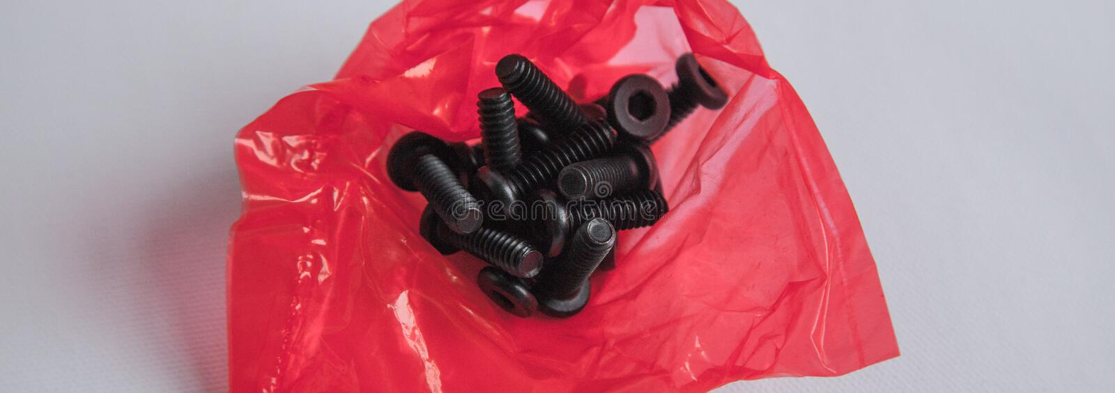 The bunch of Bolts in the red plastic bag royalty free stock image