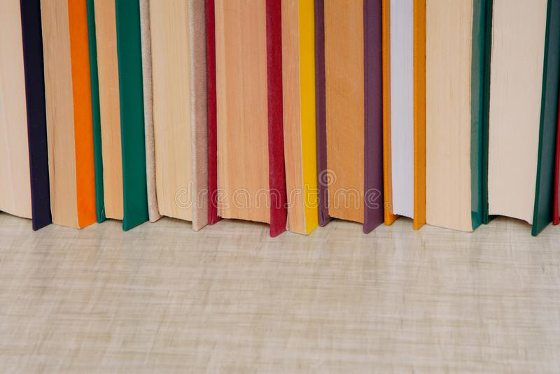 Bunch of books is on grey table, empty space for text, stack of stock images