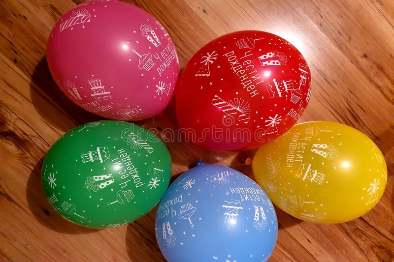 Bunch of bright balloons party. Colorful carnival or party background of balloons, streamers and confetti on wooden parquet royalty free stock photography
