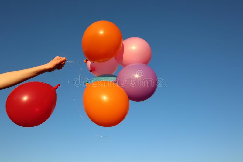 Bunch of Bright Colourful Balloons Against Blue Sky. Background held by arm in sunshine royalty free stock photo
