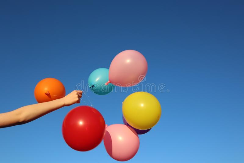 Bunch of Bright Colourful Balloons Against Sky on a Beautiful Day. Bunch of bright colourful balloons against blue sky background held by arm in sunshine on a royalty free stock photography