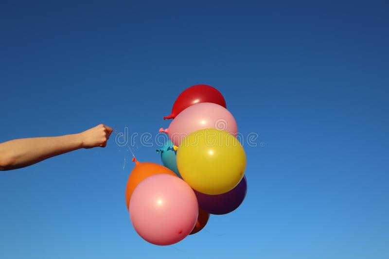Bunch of Bright Colourful Balloons Against Blue SkyHeld by Arm. Bunch of bright colourful balloons against blue sky background held by arm in sunshine on a stock images