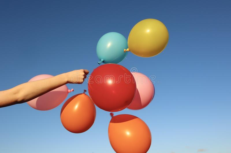 Bunch of Bright Colourful Balloons Against Sky. Bunch of bright colourful balloons against blue sky background held by arm stock images