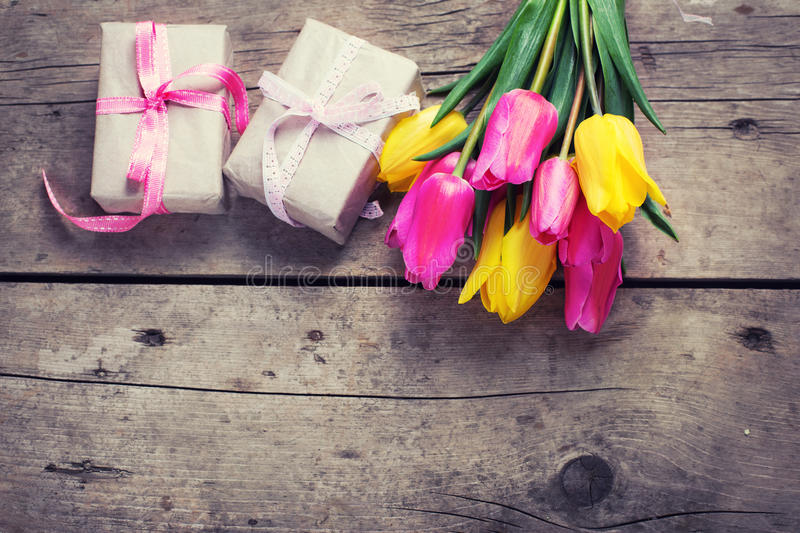 Bunch of bright yellow and pink spring tulips and boxes with presents on vintage wooden background. Selective focus. Place for text. Flat lay. Top view. Toned royalty free stock photography