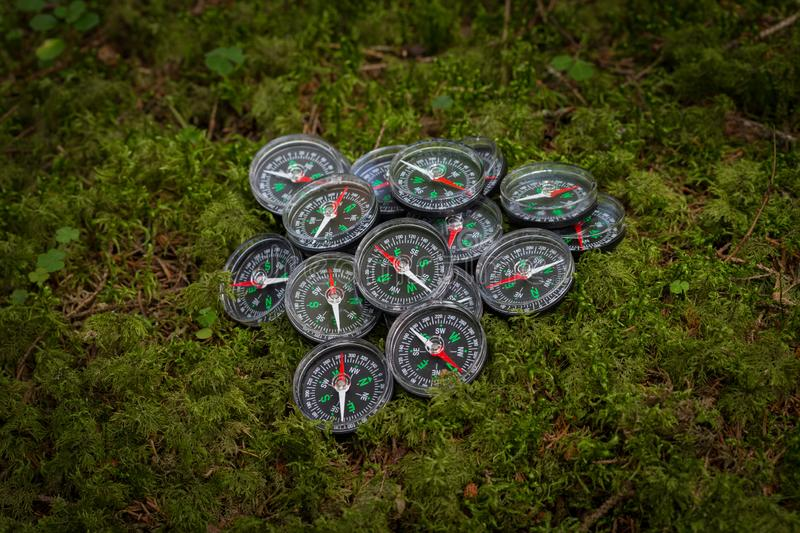 A bunch of broken compasses lying on ground in the forest. Hiking. Adventure stock photo