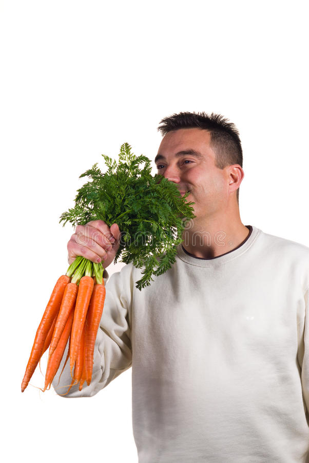 Bunch of carrots. Guy happily holding a bunch of carrots, dieting concept royalty free stock photos